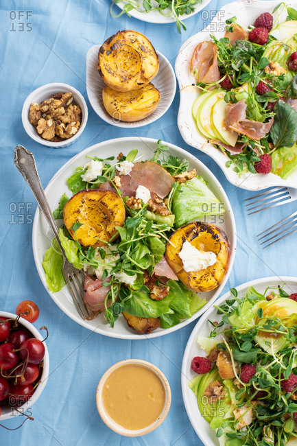 Overhead image of summer lunch with various seasonal salads and dressings. Raspberry proscuitto salad and grilled peaches mozarella salad