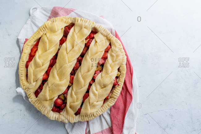 Uncooked rhubarb strawberry pie decorated with braided lattice