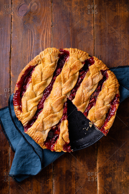 Perfect rhubarb strawberry pie decorated with braided lattice on wooden table