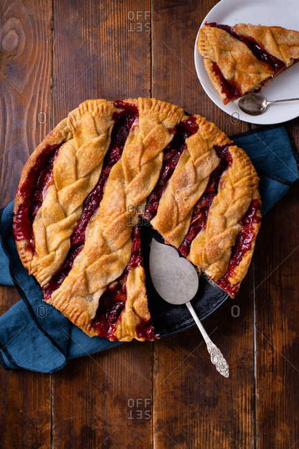 Homemade rhubarb strawberry pie decorated with braided lattice on wooden table