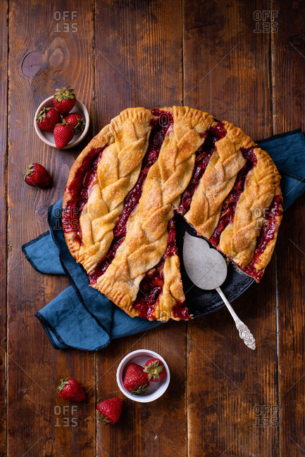 Fresh rhubarb strawberry pie decorated with braided lattice on wooden table
