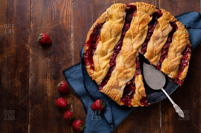Overhead view of rhubarb strawberry pie decorated with braided lattice on wooden table