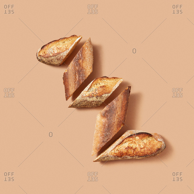 Top view of slices of fresh bread arranged in zigzag on beige background