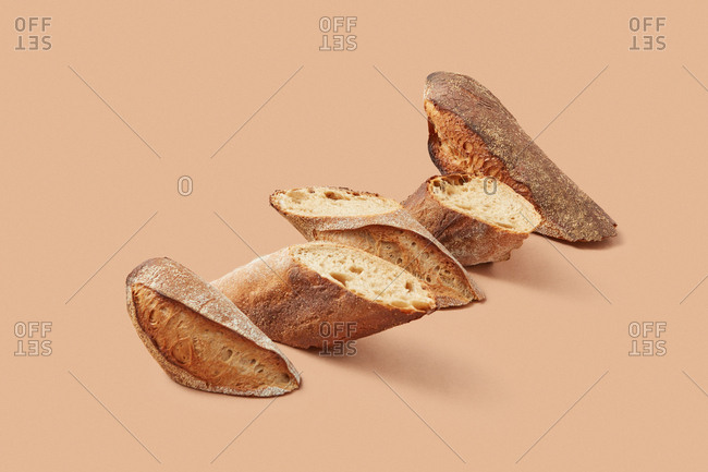 Small slices of crunchy bread arranged in diagonal line against beige background