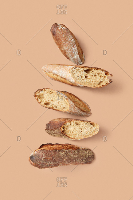 From above composition of slices of tasty fresh bread with crunchy crust against beige background