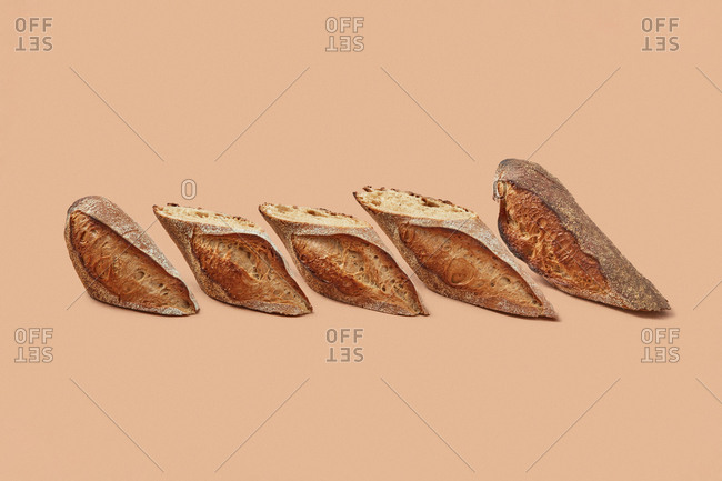 Slices of delicious bread with crunchy crust placed in row against beige background