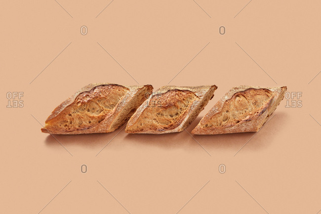 From above pieces of fresh yummy bread arranged in line against beige background