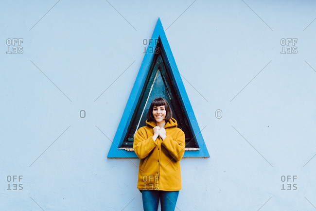 Young woman in yellow warm coat smiling and looking at camera while standing against triangle window and gray wall of building