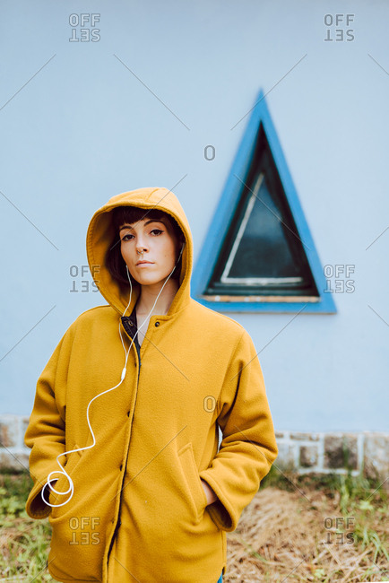 Young woman in yellow warm coat listening to the music and looking at camera while standing against triangle window and gray wall of building