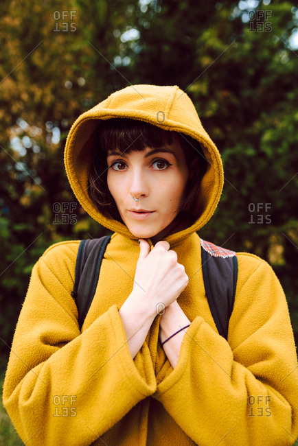 Shivering female wrapping in yellow hooded coat and looking at camera while standing on blurred background of nature in cold day