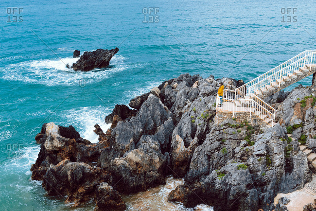 Side view of anonymous lady admiring waving and crashing blue sea water in bay while standing on stairway on cliff