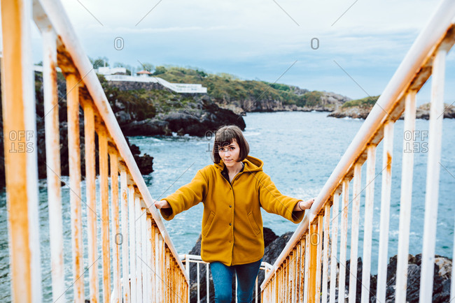 Young female in yellow jacket standing on rusty stairway against bay with waving sea water