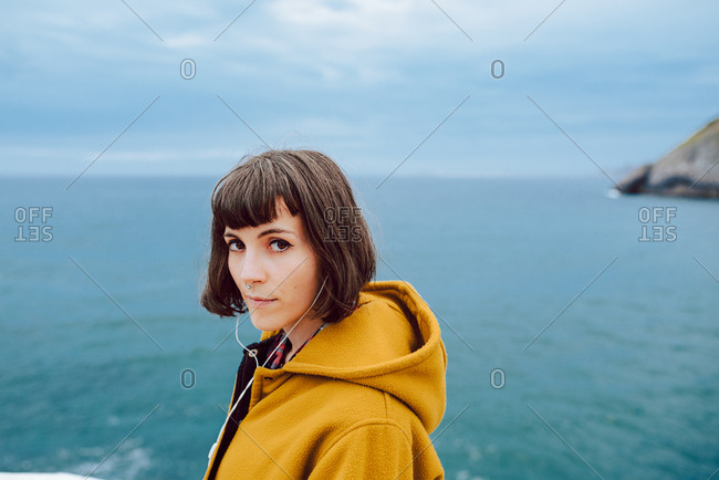 Pretty female in yellow warm jacket looking at camera while standing against rippling sea and overcast sky in nature