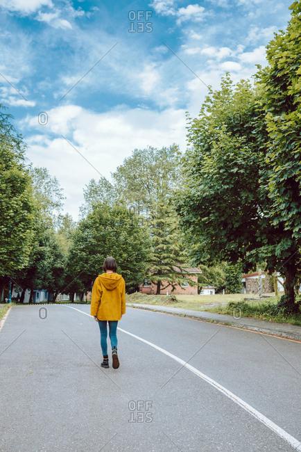 Back view of female in yellow coat walking along asphalt road on green suburban street