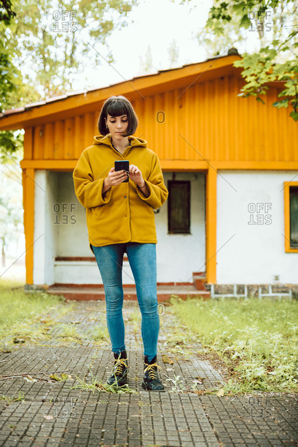 Young female in casual outfit smiling and browsing smartphone while standing on tiled path outside lovely cottage on autumn day in countryside
