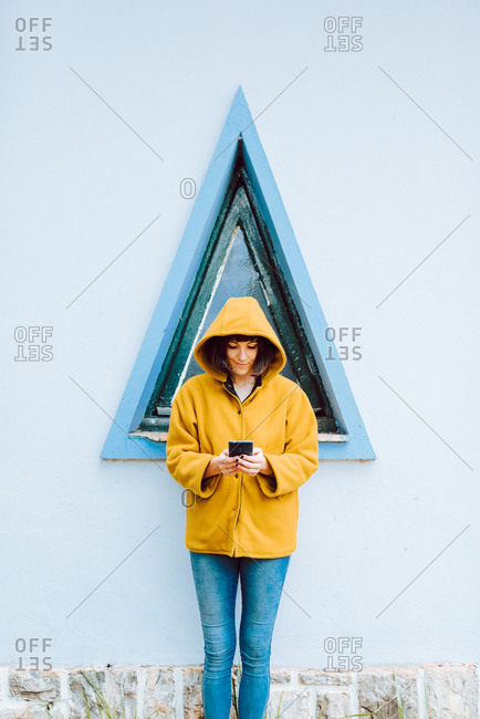 Young woman in yellow warm coat smiling and looking down while standing against triangle window and gray wall of building