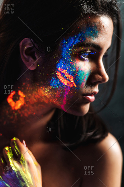 Side view of beautiful young woman covered with luminous paint on face, neck and hand looking away.