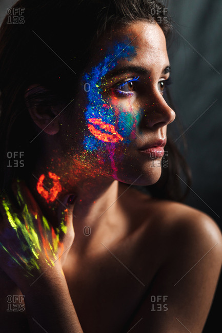 Portrait of beautiful young woman covered with luminous paint on face, neck and hand looking away.
