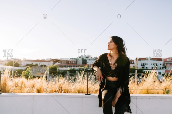 Beautiful stylish woman in black outfit standing by bridge with city landscape in lisbon on sunny day