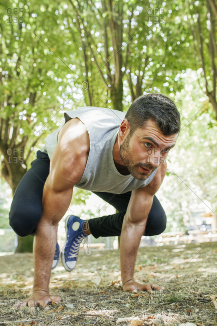 Handsome focused muscular man in sportswear doing exercise in park on sunny day