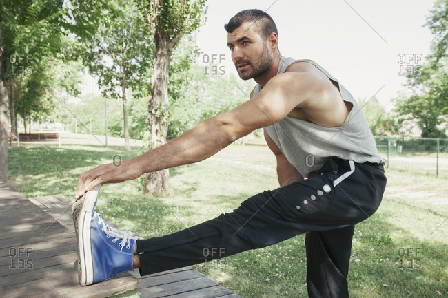 Adult concentrated muscular man in sportswear stretching body muscles in sunny park