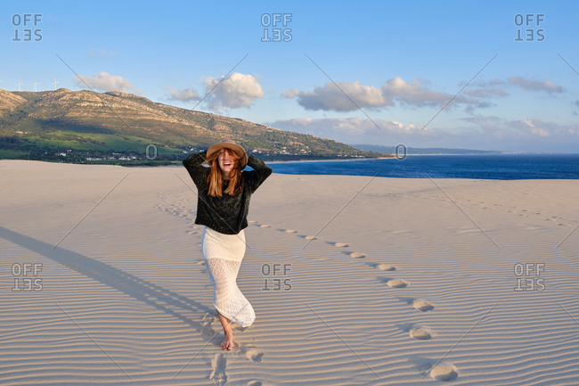 Cheerful traveling woman in hat standing in remote sandy desert on sunset looking at camera in tarifa, spain