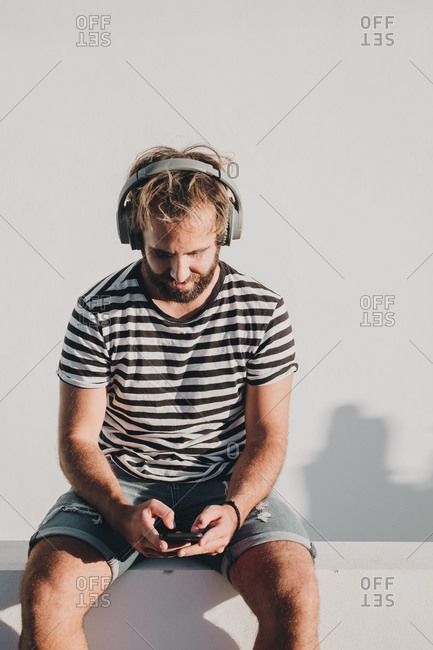 Young male sitting with smartphone and headphones