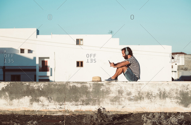 Side view of man listening to music and using mobile phone while relaxing on embankment in la restinga