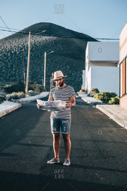 Male traveler standing with map