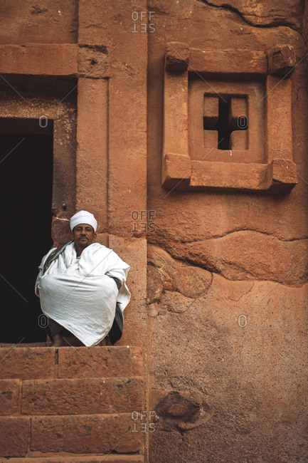Lalibela, Ethiopia - November 04, 2018: Priest sitting on porch of old rock-hewn orthodox church