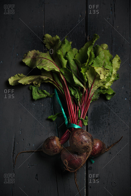 From above dark red sugar beetroots on stem with green leaves on black background