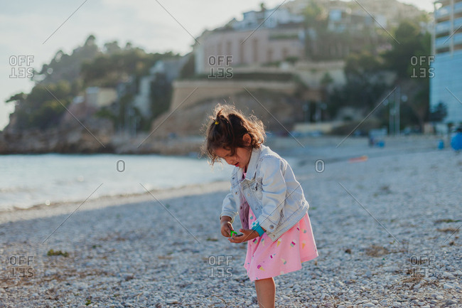 Little brunette girl in jacket jeans and pink dress playing with toy shovel at rocky sea shore
