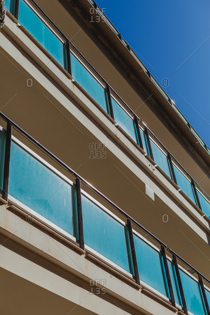 From below of facade of hotel with open glass balconies in sunny weather