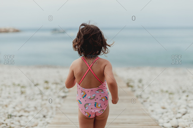 Back view of anonymous child in pink bathing suit running along wooden jetty by sea