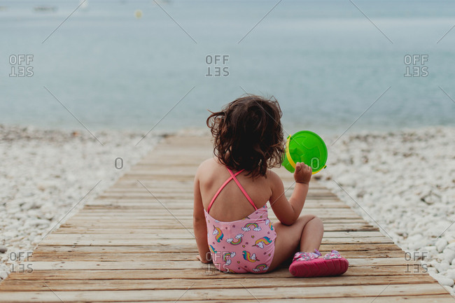 Back view of anonymous child in pink bathing suit holding a toy bucket while sitting on wooden jetty by sea
