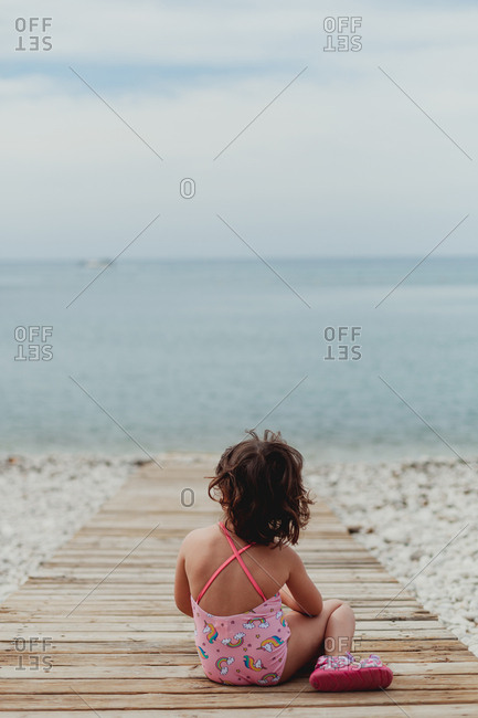Back view of anonymous child in pink bathing suit sitting on wooden jetty by sea