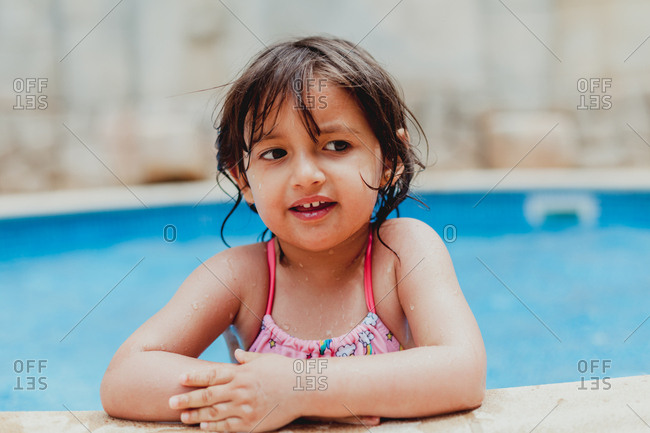 Kid bathing while leaning on edge of pool with clear blue water and looking away