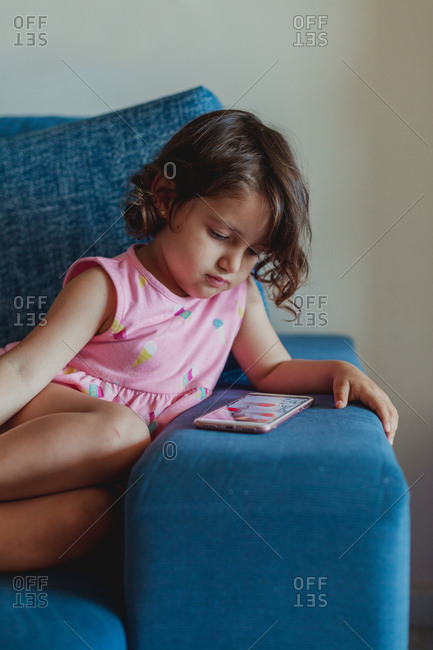 Adorable little brunette girl in pink dress sitting on sofa and watching cartoons on mobile phone at home