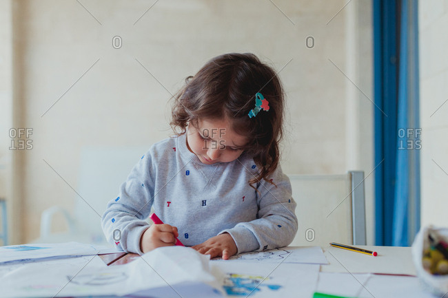 Cute curly little brunette girl in gray sweater enthusiastically drawing pencil on paper at home