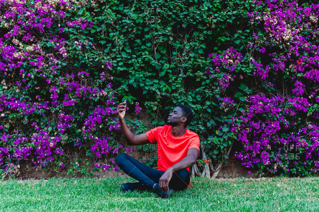 Slim african american sportsman sitting on green meadow near hedge with purple flowers on the mobile phone
