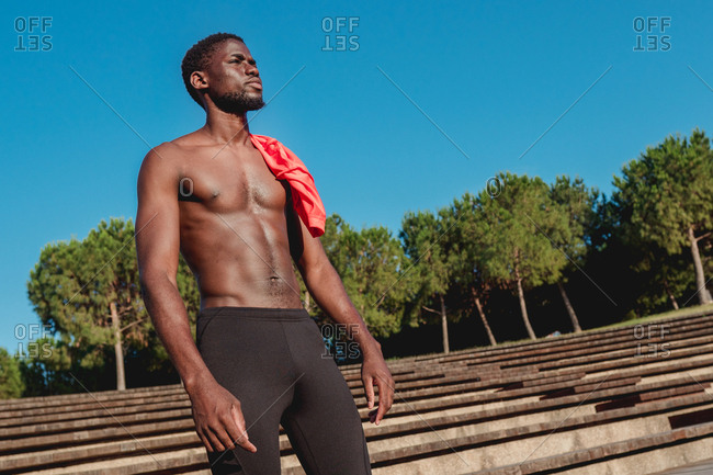 Strong athletic shirtless african american man standing near stairs in bright hot day