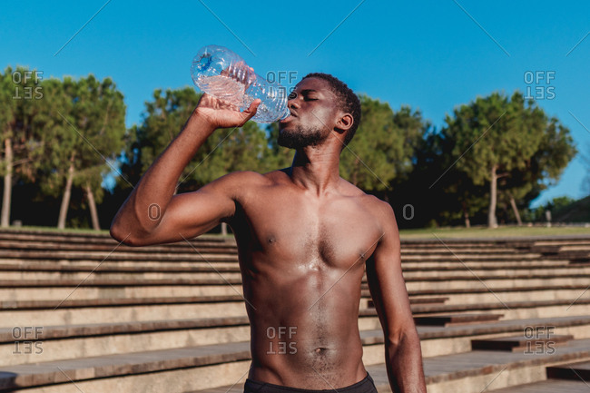 Strong athletic african american man drinking water from plastic bottle in bright hot day