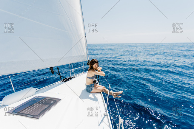 Side view of traveling woman wearing swimsuit sitting on side of yacht in sea looking away