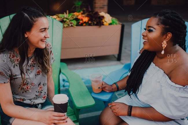From above side view cheerful multiracial young casual women talking and drinking coffee while sitting by vibrant table at hipster cafe