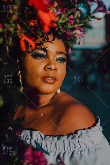 Attractive black stylish young woman in off-shoulder dress enjoying sunshine while standing on street beside blossomed tree looking away