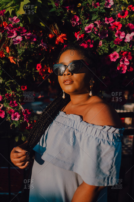 Attractive black stylish young woman in off-shoulder dress and sunglasses enjoying sunshine while standing on street beside blossomed tree