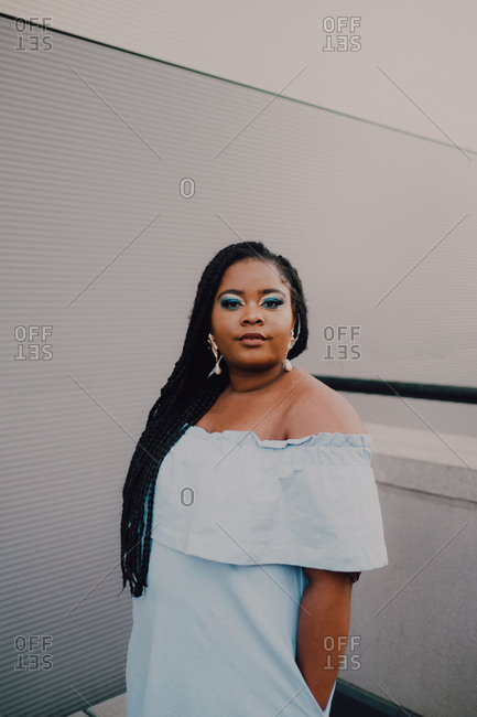 Attractive black young woman with bright makeup in off-shoulder dress standing on empty wall looking at camera