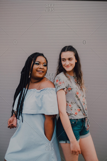 Multiracial young casual women laughing and hugging while standing on street wall