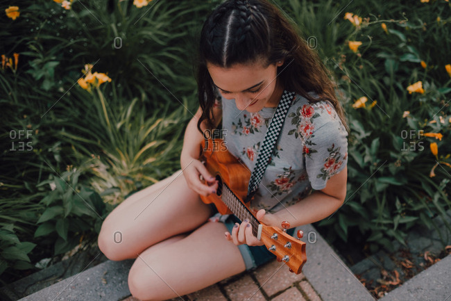 From above smiling trendy casual young woman in t-shirt playing ukulele while sitting in pavement beside flowerbed