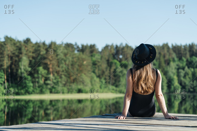 Back view of unrecognizable thoughtful woman in black swimsuit and hat sitting on wooden pier and admiring view of lake on clear blue sky and forest background